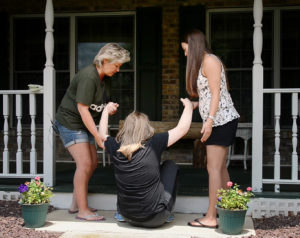 Rebecca Droke/Post-Gazette--Tuesday, June 21, 2016-- STORY BY KATE GIAMMARISE--Sandy Etling, left, and habilitation aid Stacy Yvanek, right, have to jointly hoist Abbey from the walkway onto the porch outside the Etling's home in Latrobe on Tuesday, June 21, 2016. Abbey now struggles to navigate steps and other changes in walking surfaces after losing the daily services she got as child with an intellectual disability and autism.