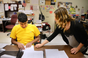 Rebecca Droke/Post-Gazette--Monday, June 13, 2016-- STORY BY KATE GIAMMARISE-- Tejus Sharathchandra(cq), 20, works with Katie Simanski, a behavorial specialist, as he folds letters for mailers at the Vocational Training Center of Western Psychiatric Institute and Clinic of UPMC on the South Side Monday, June 13, 2016. His ability to work at the vo-tech center and receive services from a behavioral therapist once he turns 21 are dependent on whether he receives waiver funding or not.