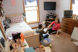 Rebecca Droke/Post-Gazette--Tuesday, May 17, 2016-- STORY BY KATE GIAMMARISE-- Stacy Yvanek, a habilitation aid, plays games with Abbey Etling, 22, to keep her engaged and create structure in her day at home in Latrobe on Tuesday, May 17, 2016. Without the consolidated waiver funding, Stacy can only come xx hours a week, far fewer hours of specialized supports Abbey needs to maintain daily living skills.